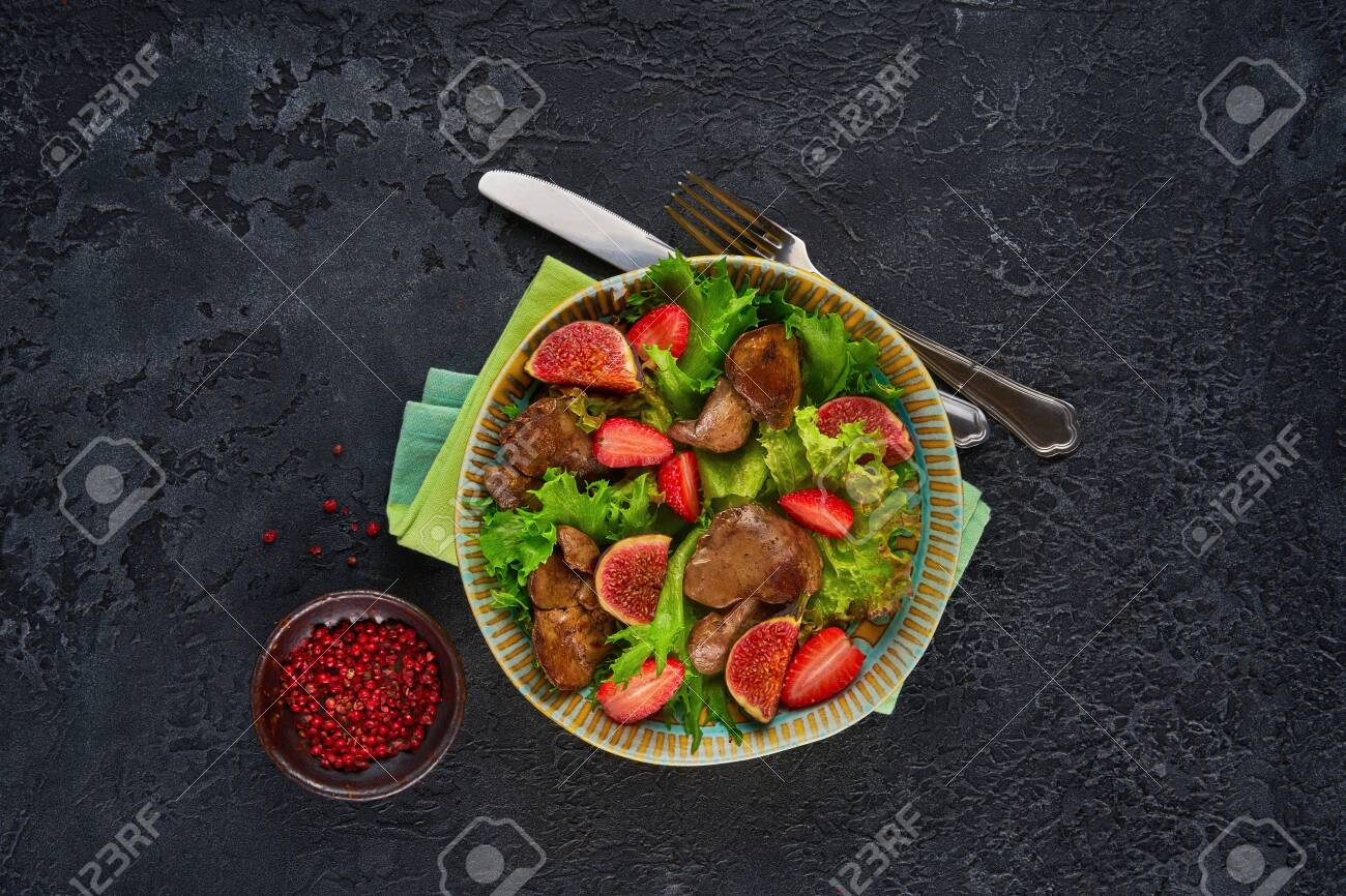 Green salad with liver and strawberry on dark rustic background - 131904889
