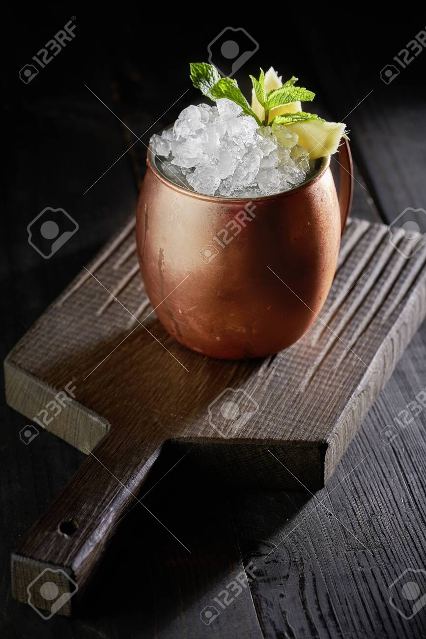 Cold Moscow Mule cocktail in copper mug on the rustic wooden background - 131305101