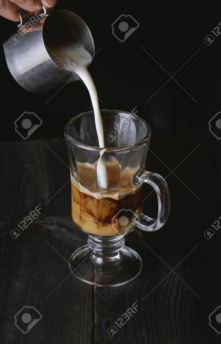 Hand pouring milk in cold brew coffee on black wooden table. - 131305989