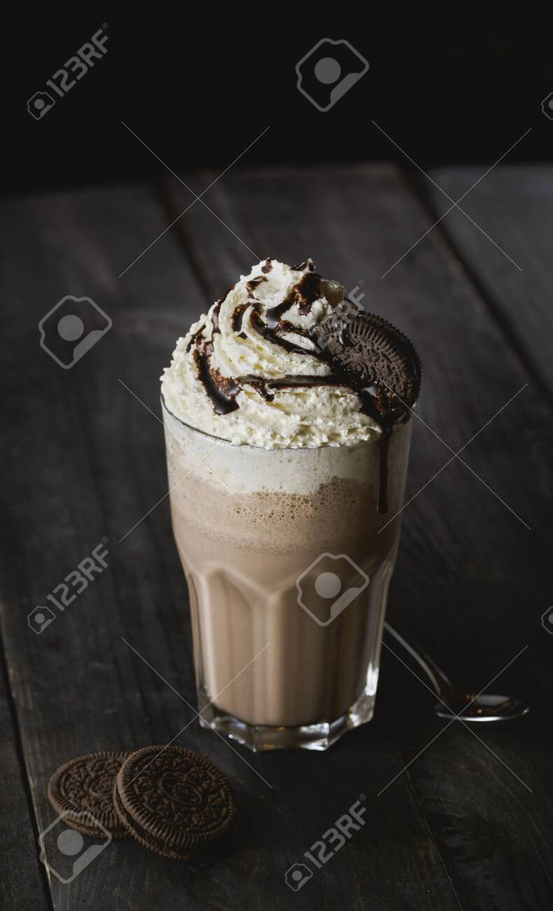 Delicious creamy milkshake with cookie on wooden table - 131306063