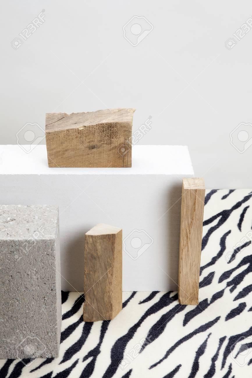 Morceau De Bois Brut 2 blocs de béton et morceau de bois brut sur un modèle de confection de  bois. couleur morte nature morte