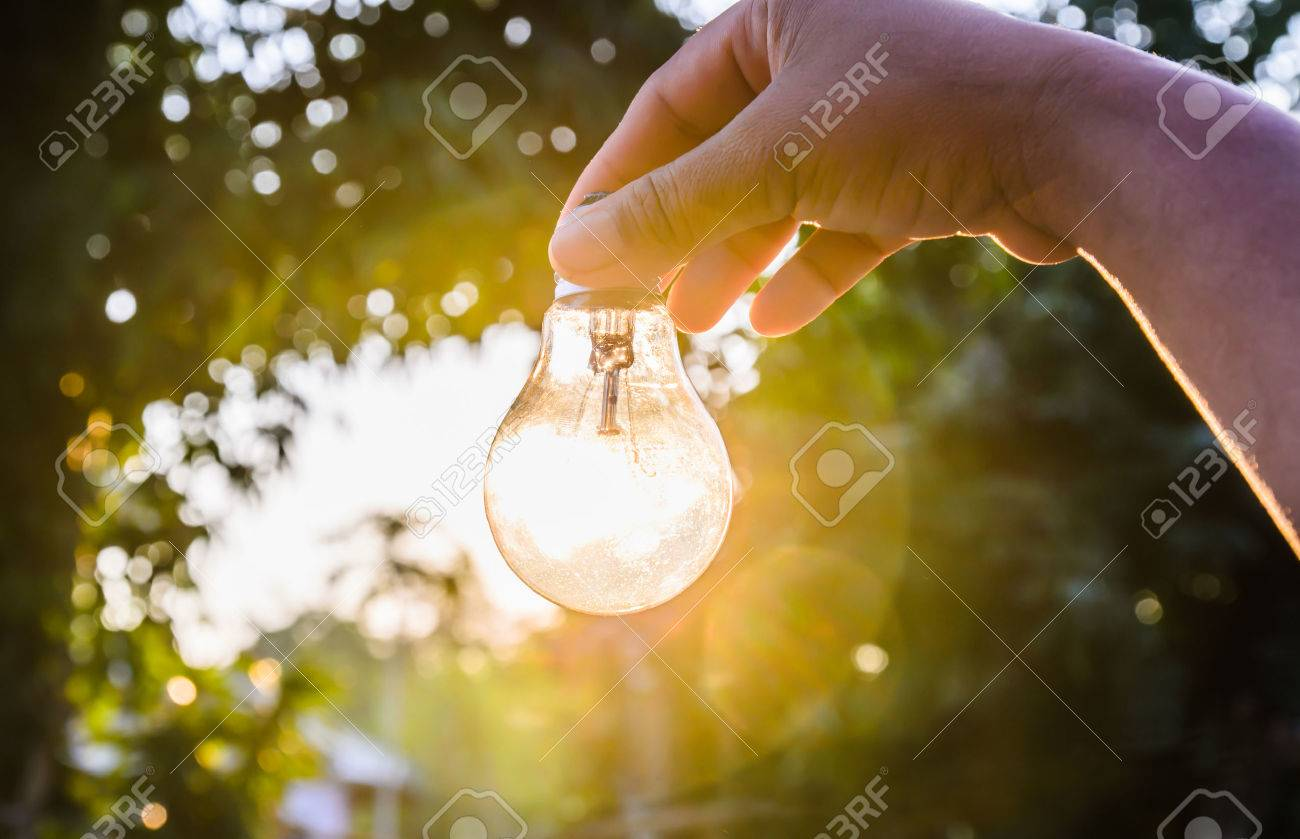 and holding a light bulb with sunset power concept - 47848313