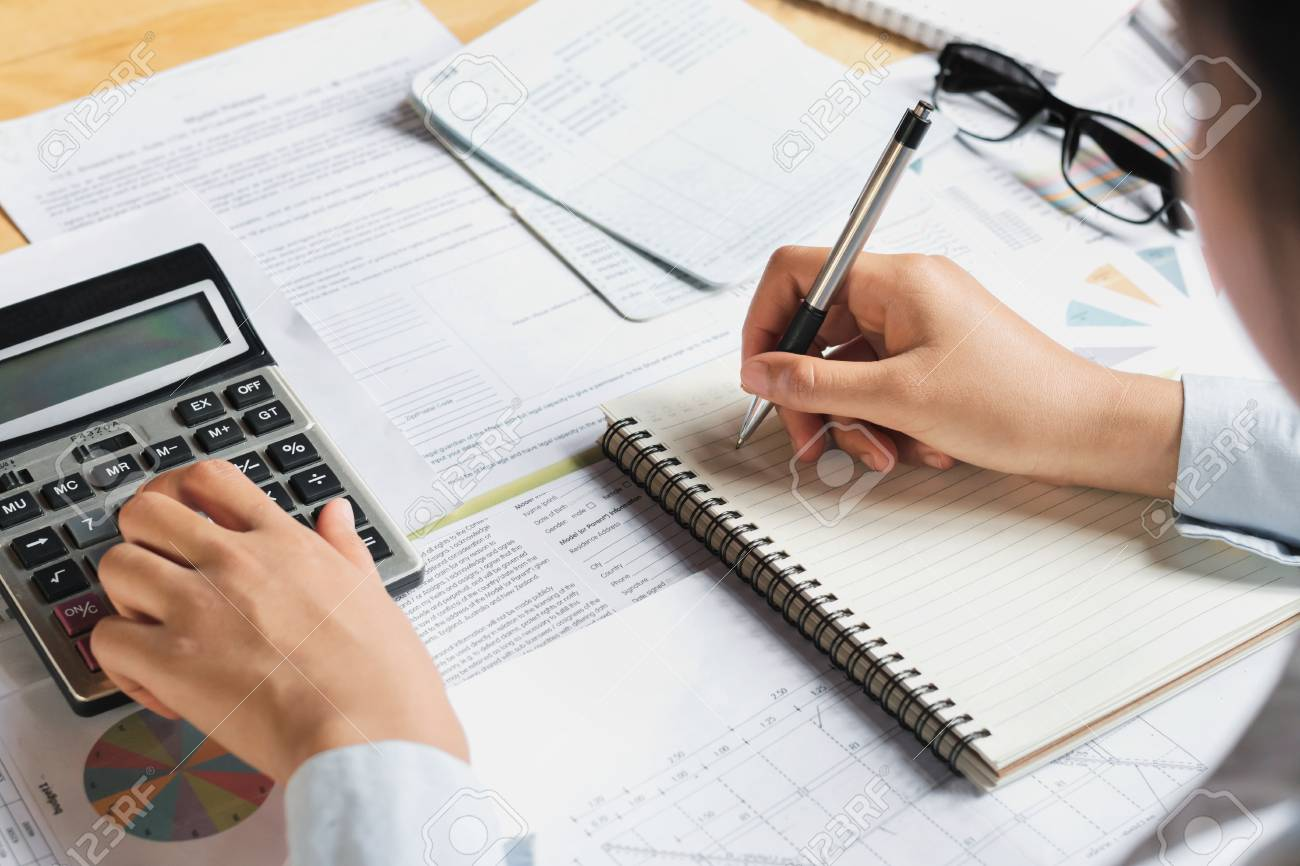 accountant using calculator for calculate budget finance on table