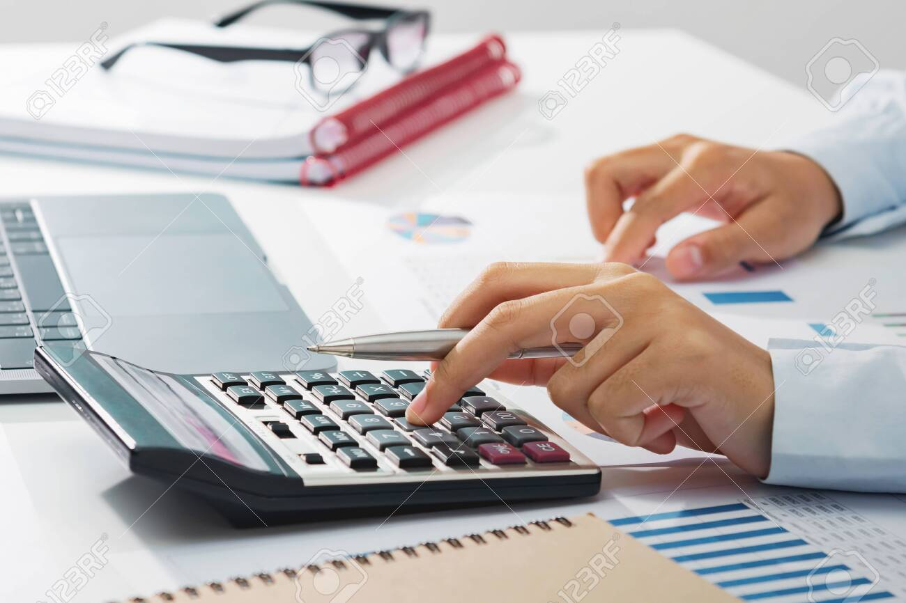 businesswoman working on desk using calculator analyzing finance accounting in office - 139288775