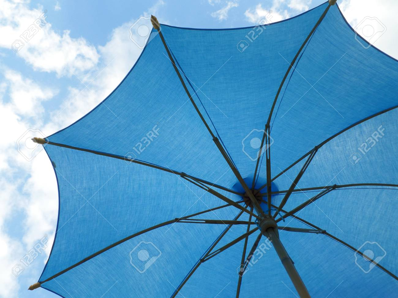 75083f6d4 One vibrant blue colored sunshade against bright blue sky and white cloud  Stock Photo - 70009397