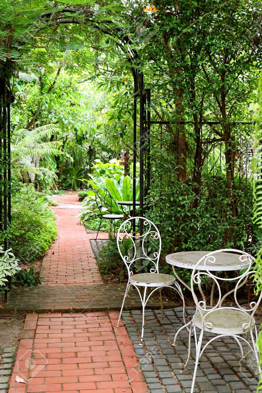 Photo verticale de la table et des chaises en fer forgé blanc dans le  jardin avec passerelle en briques pavées
