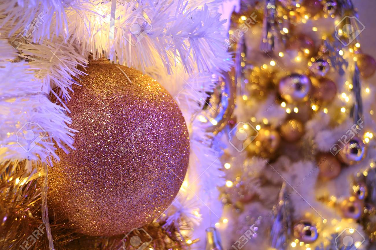 Closed up pink gold glitter ball shaped Christmas ornament with