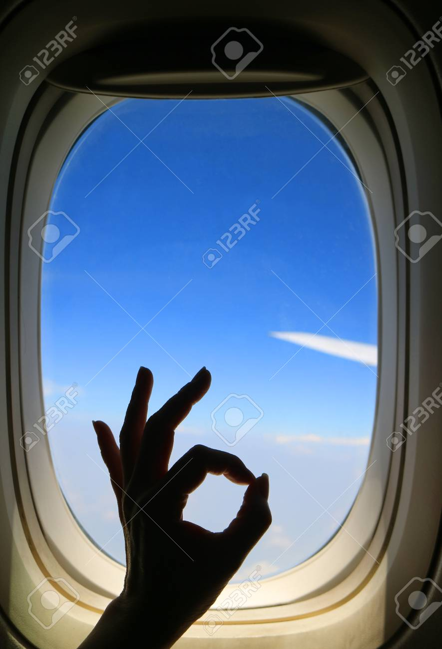 Silhouette Of Female S Hand Posing Ok Sign Against Airplane Window