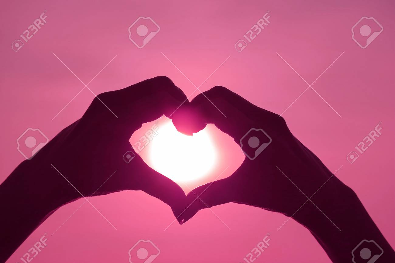 Pink Colored silhouette of female's hand posing LOVE HEART sign against shiny sun - 124742269
