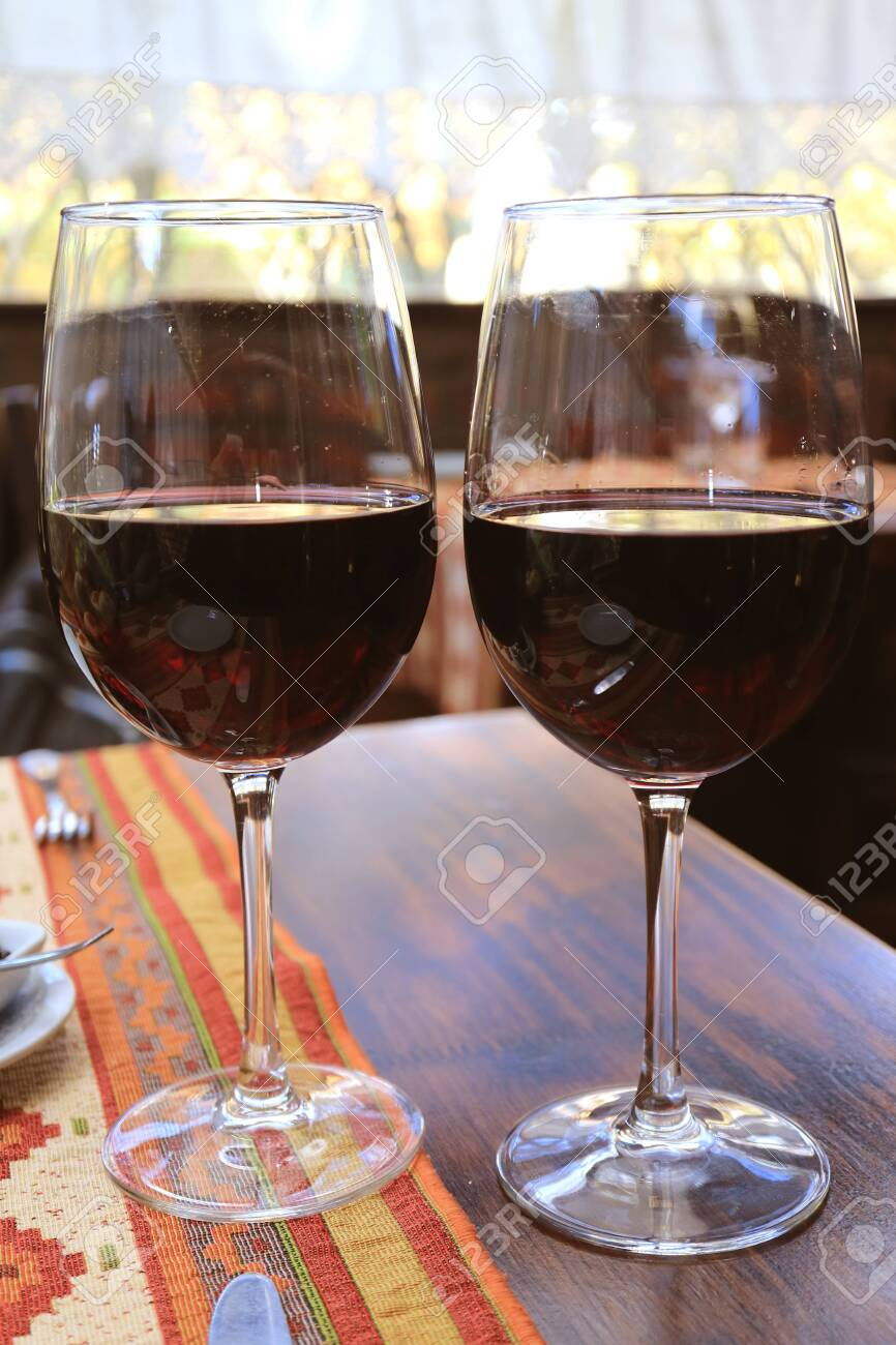 Vertical image of two glasses of red wine on the table in restaurant - 138504497