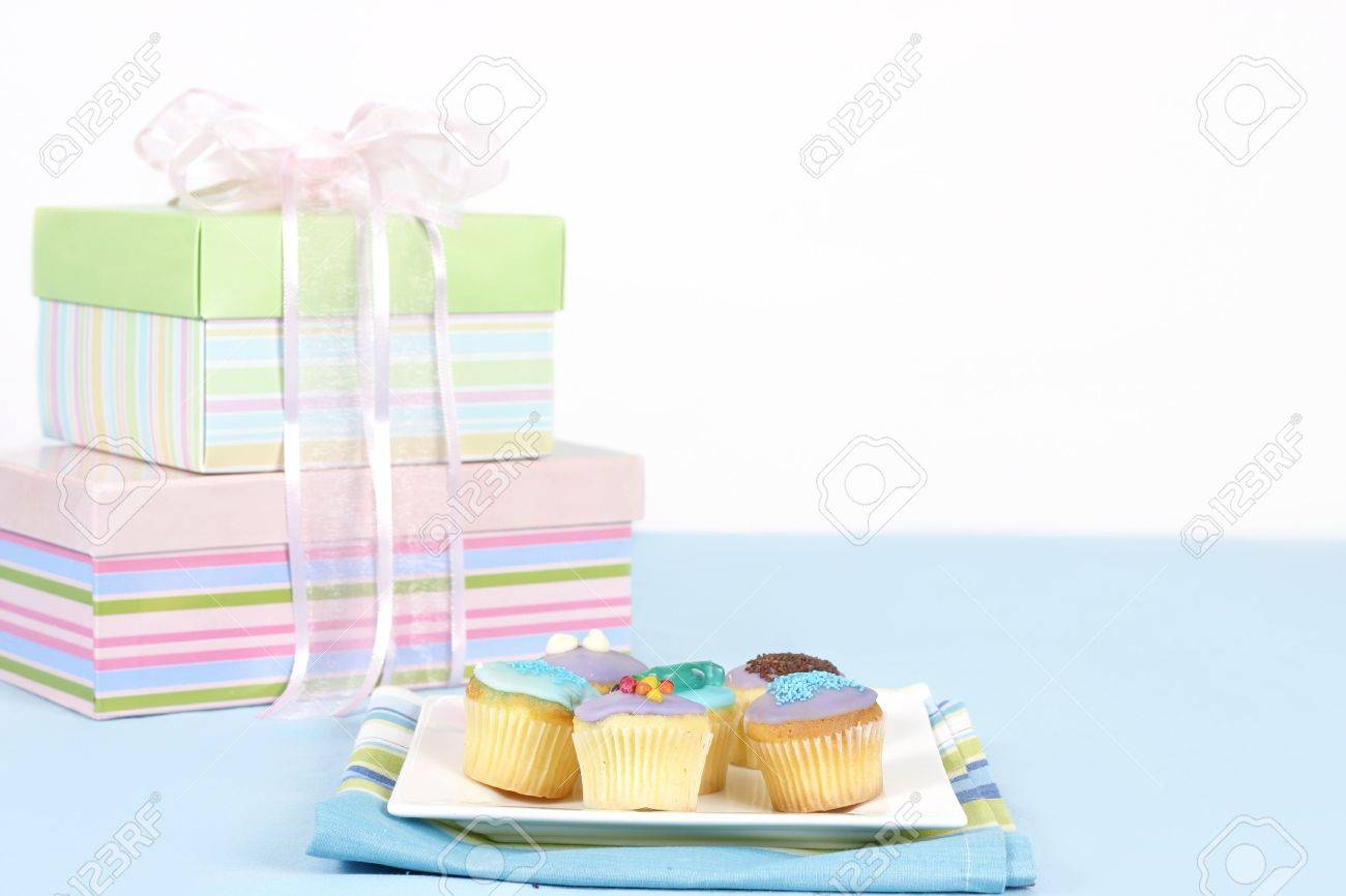 Miniature cakes sitting on a white plate on a blue tablecloth.  Pastel boxes tied with pale pink satin and gauze ribbon in backgound.  Focus is to the foreground and cakes only.  Space for a message. Stock Photo - 287565