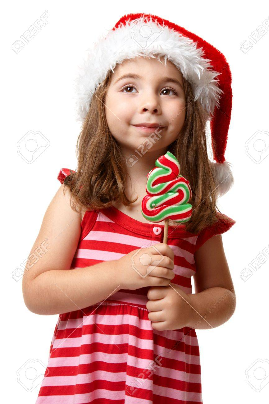 Little girl wearing a  red santa hat and striped dress.  She is holding a christmas tree lollipop candy on a stick Stock Photo - 5485761