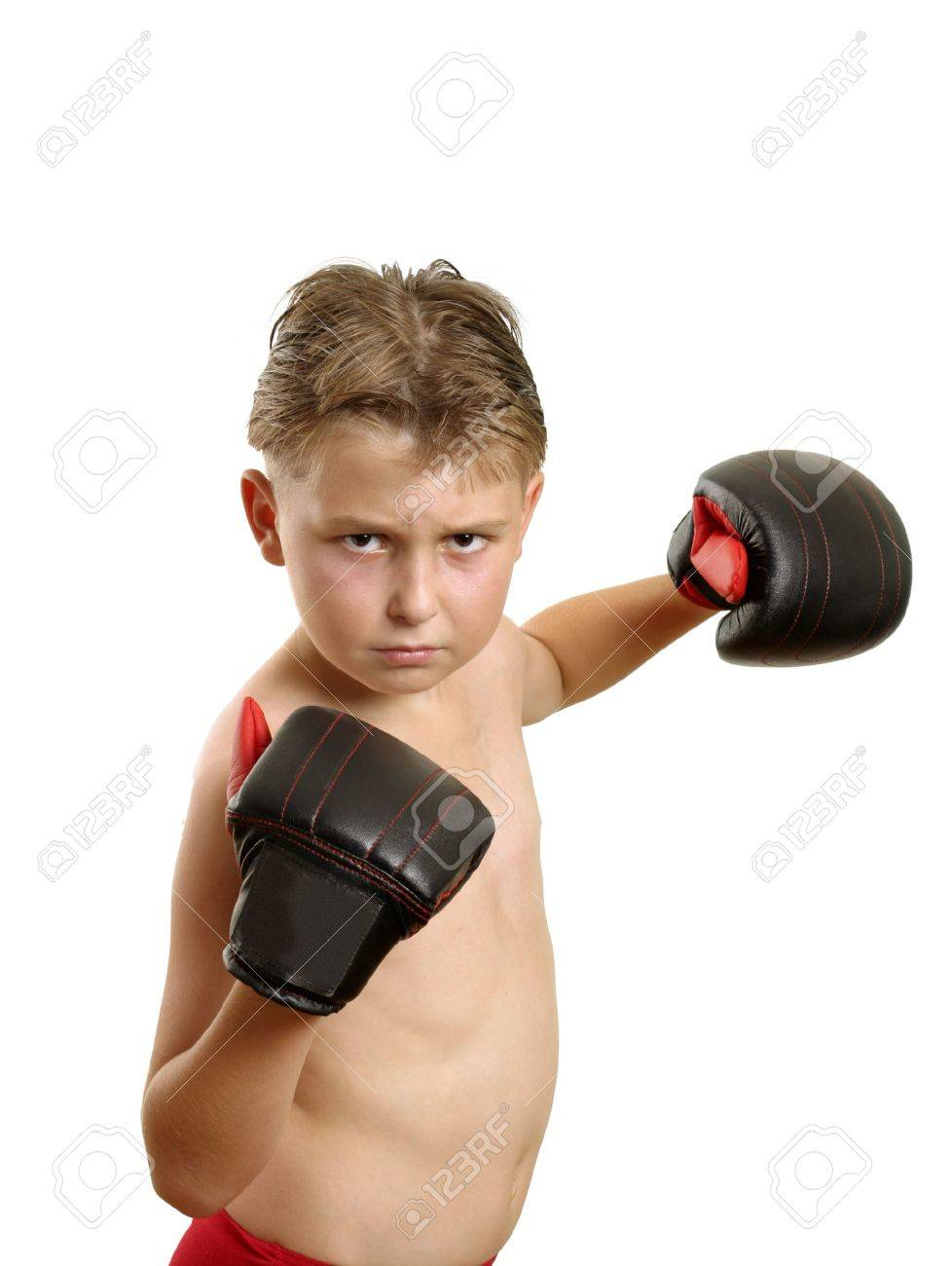 Boy in boxing gloves throwing some punches. Stock Photo - 6141270