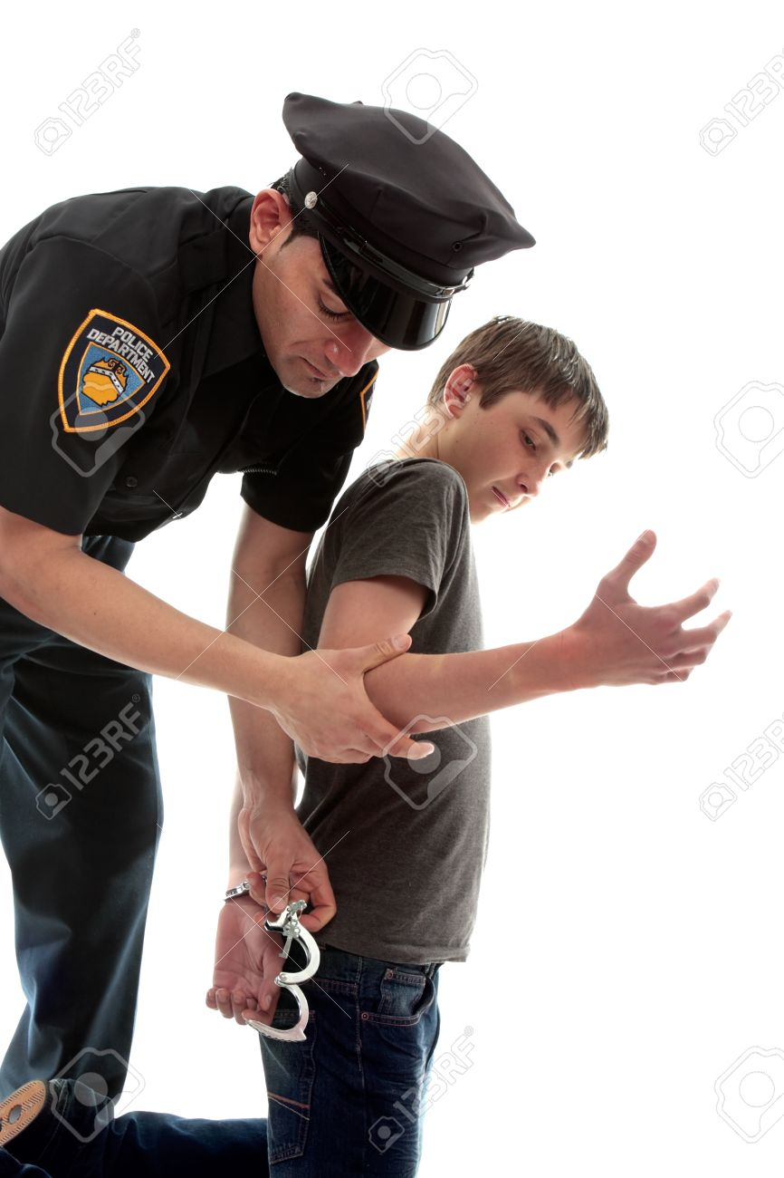 A uniformed policeman arrests and handcuffs a young teen criminal Stock Photo - 10438935