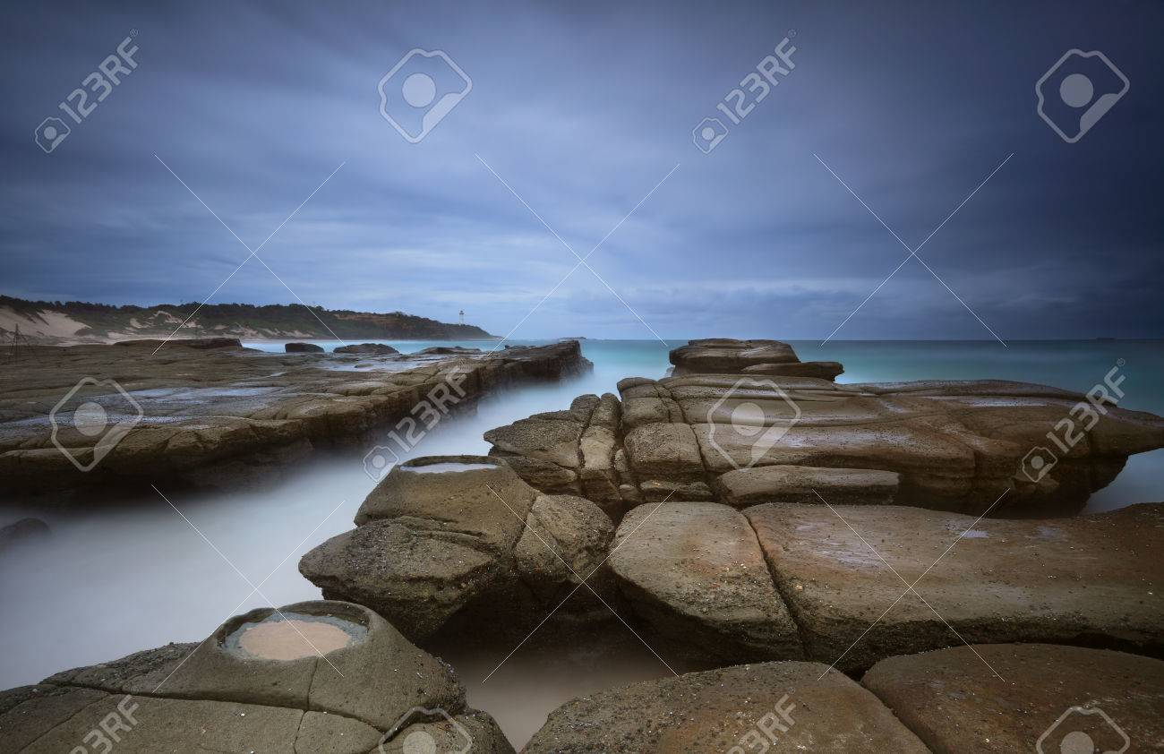 weathered rocks ocean channel and rock craters at soldiers beach weathered rocks ocean channel and rock craters at soldiers beach australia under a stormy dark
