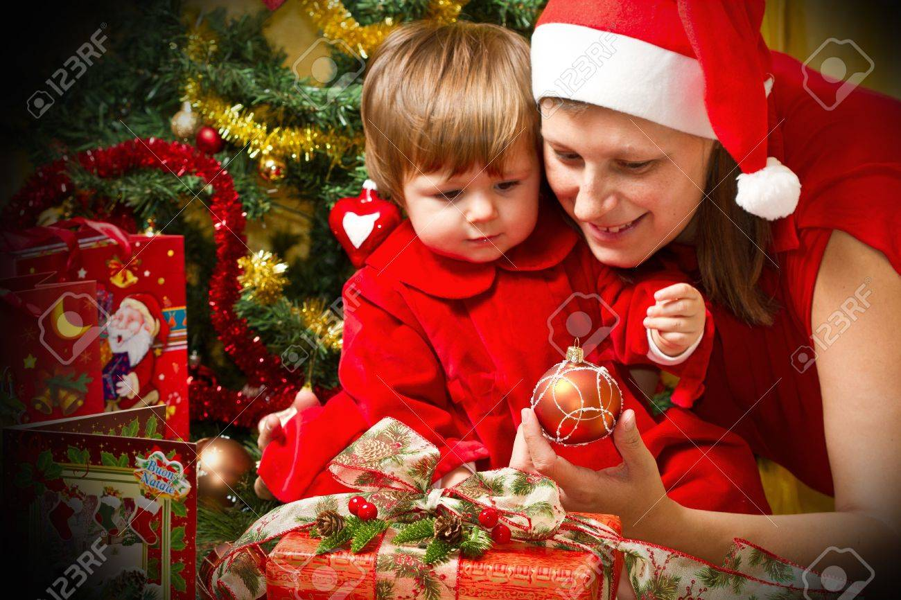 Young motherwith  baby  at Christmas tree Stock Photo - 16010369