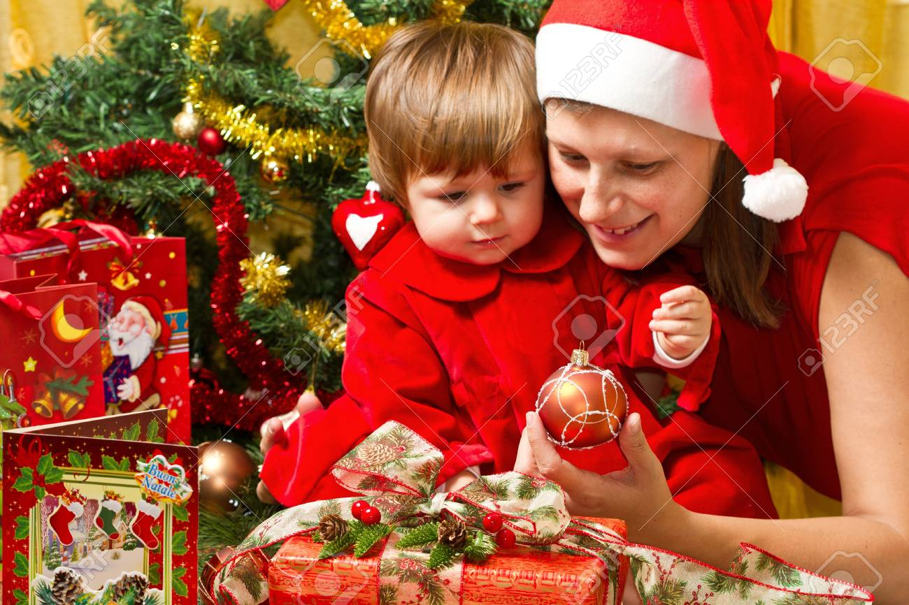 Young motherwith  baby  at Christmas tree Stock Photo - 16519274