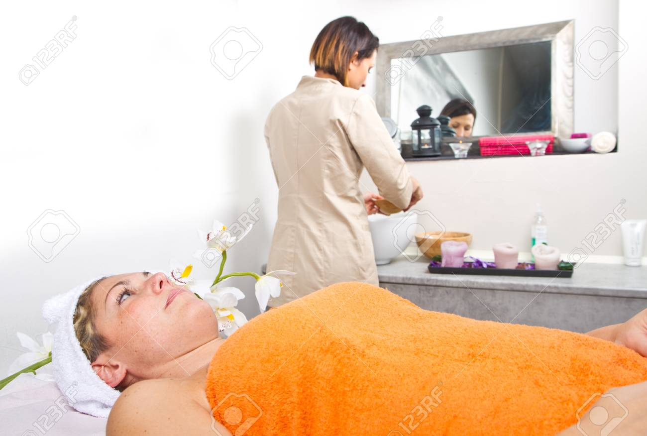 Therapist applying a face mask to a beautiful young woman in a spa using a cosmetics brush Stock Photo - 23568858