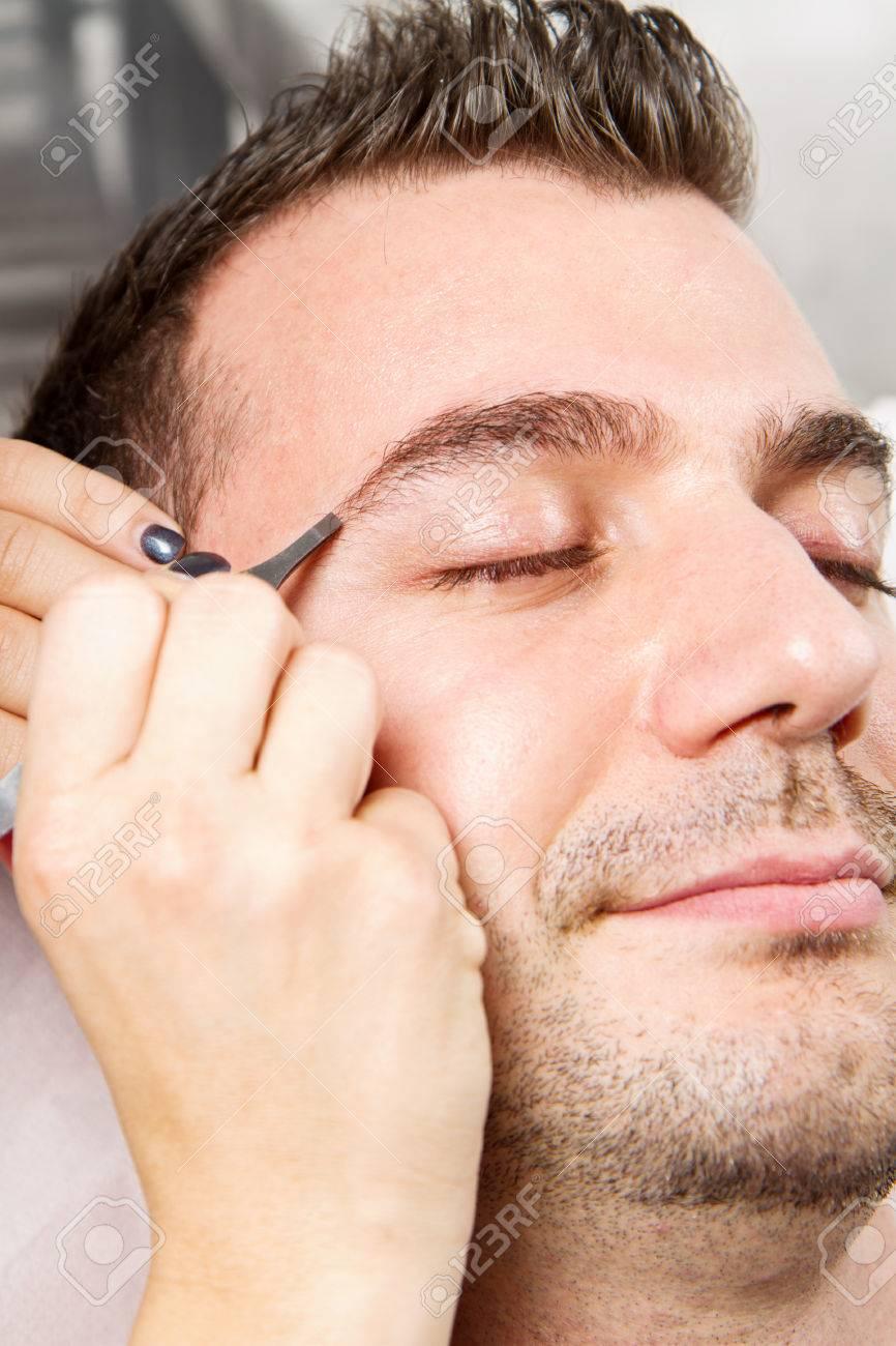 Cejas De Hombre esteticista depilarse las cejas un hermoso hombre con pinzas en un salón de  belleza