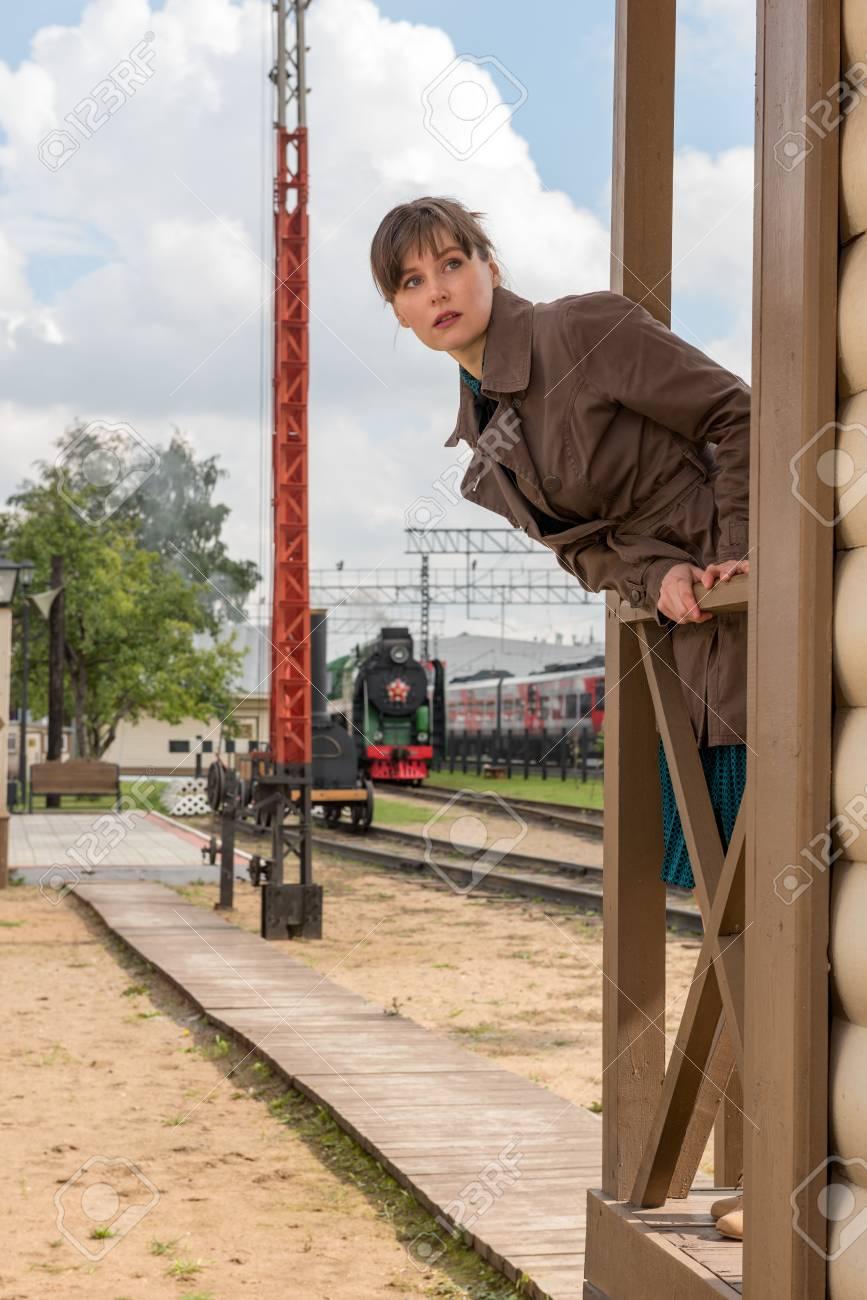 Giovane donna in attesa di arrivo di un treno in una piccola stazione in stile retrò