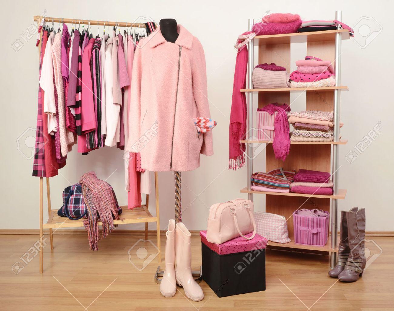 vestir armario con ropa de color rosa dispuestas sobre perchas y estantes un abrigo en