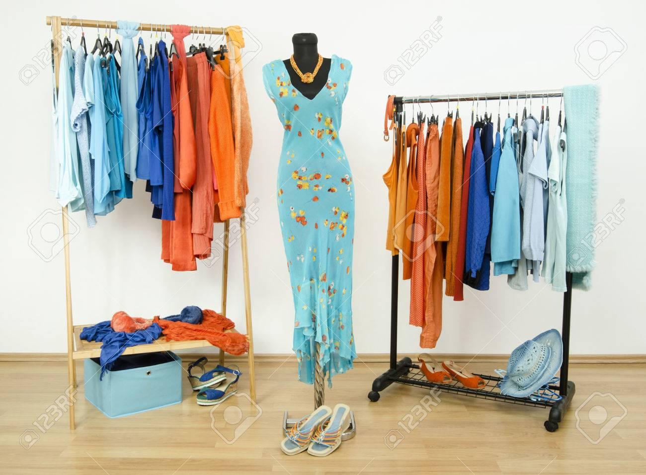 armario con colores naranja y ropa azules dispuestas en perchas vestir armario con ropa