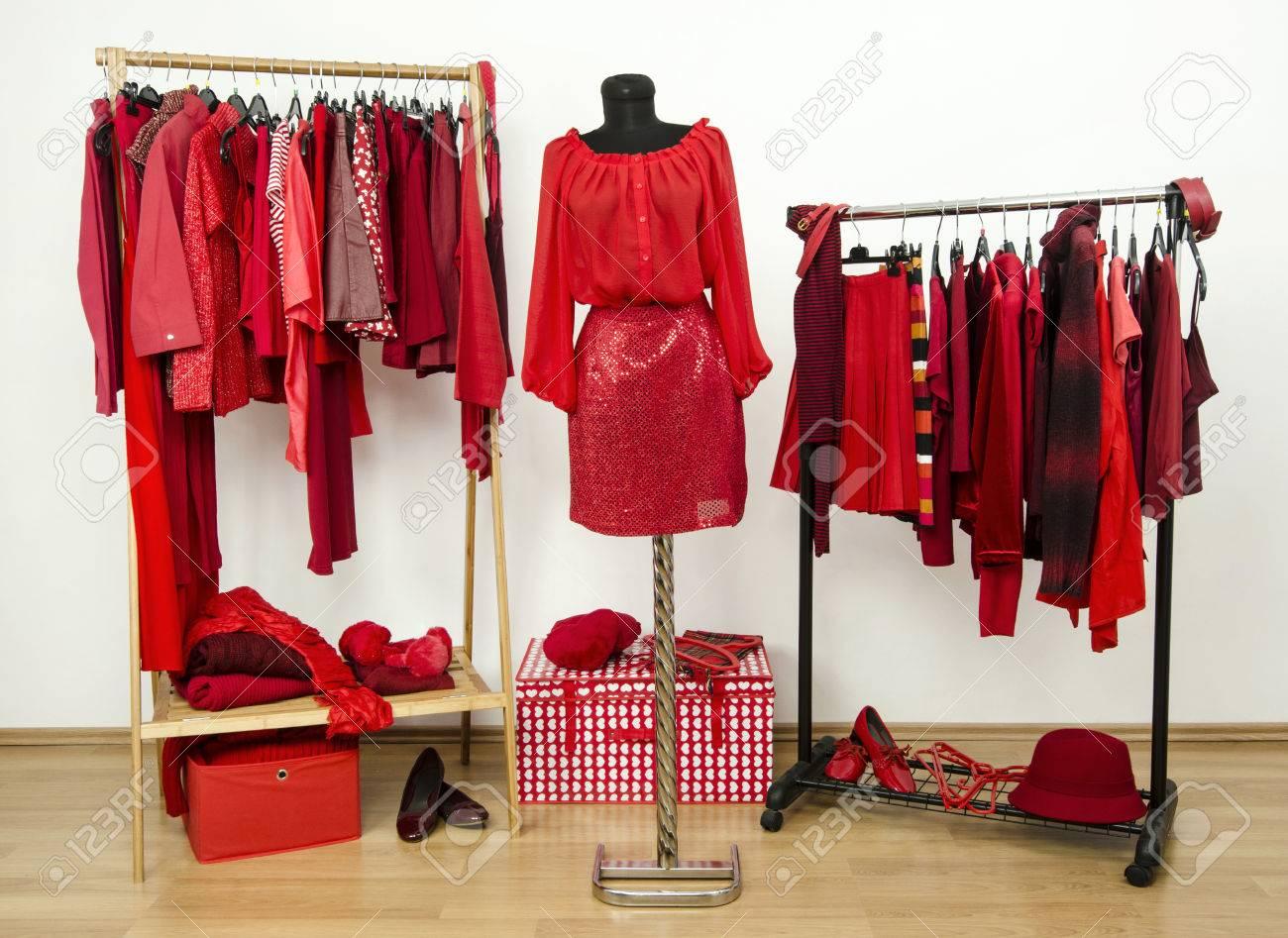 foto de archivo vestir armario con ropa de color rojo dispuestas en perchas y un traje en un maniqu armario lleno de todos los matices de la ropa de