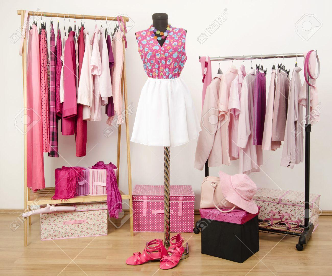 62a171ea433e Foto de archivo - Vestir armario con ropa de color rosa dispuestas sobre  perchas y un traje en un maniquí. Armario lleno de todos los tonos de ropa  de color ...