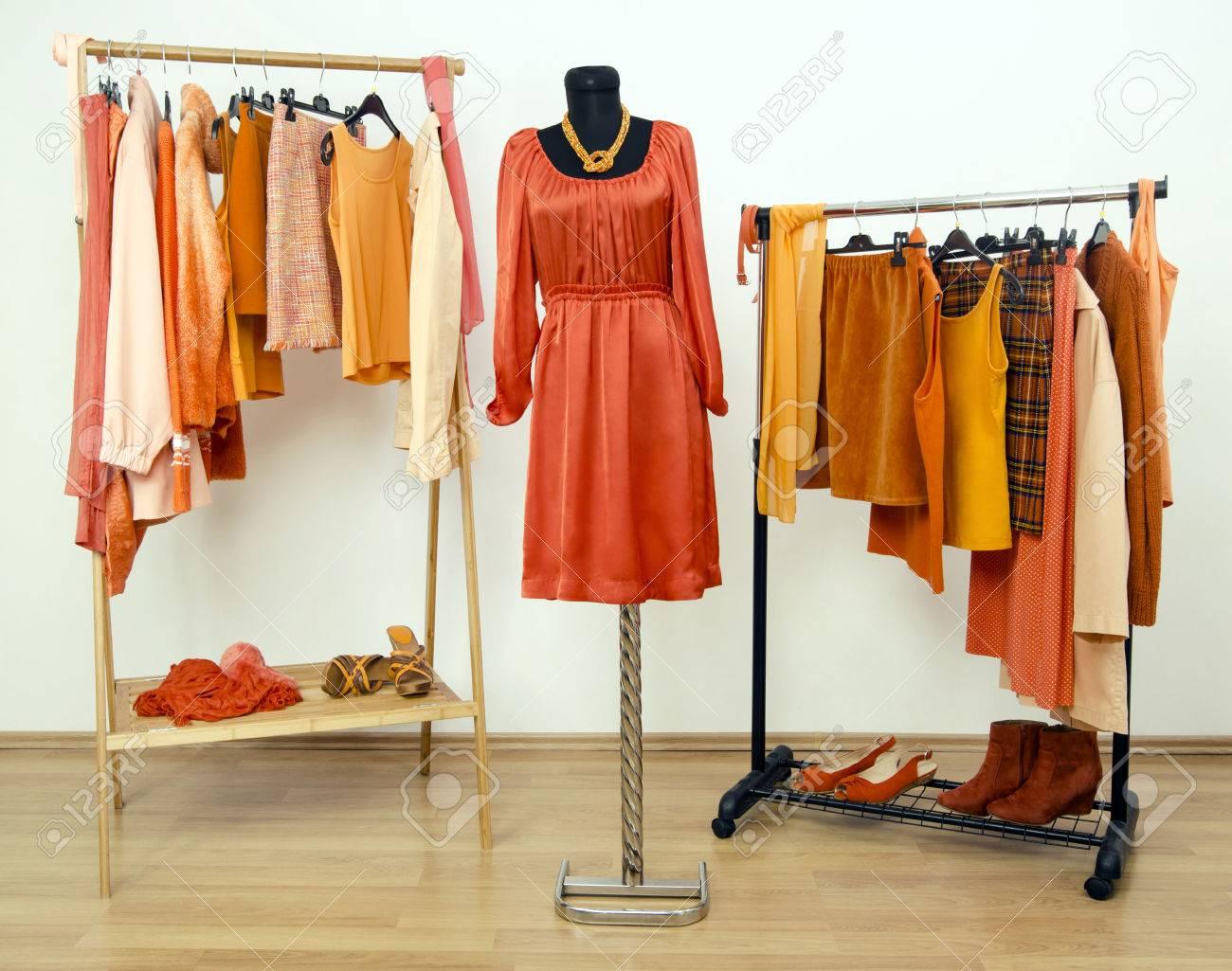 vestir armario con ropa de color naranja dispuestos en perchas y un vestido en un maniqu
