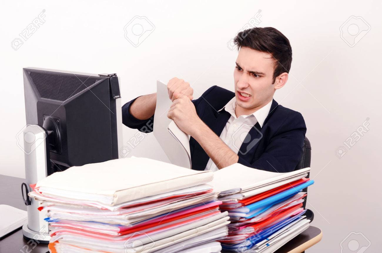 angry business man tearing up paper work unhappy worker angry business man tearing up paper work unhappy worker a big pile of files