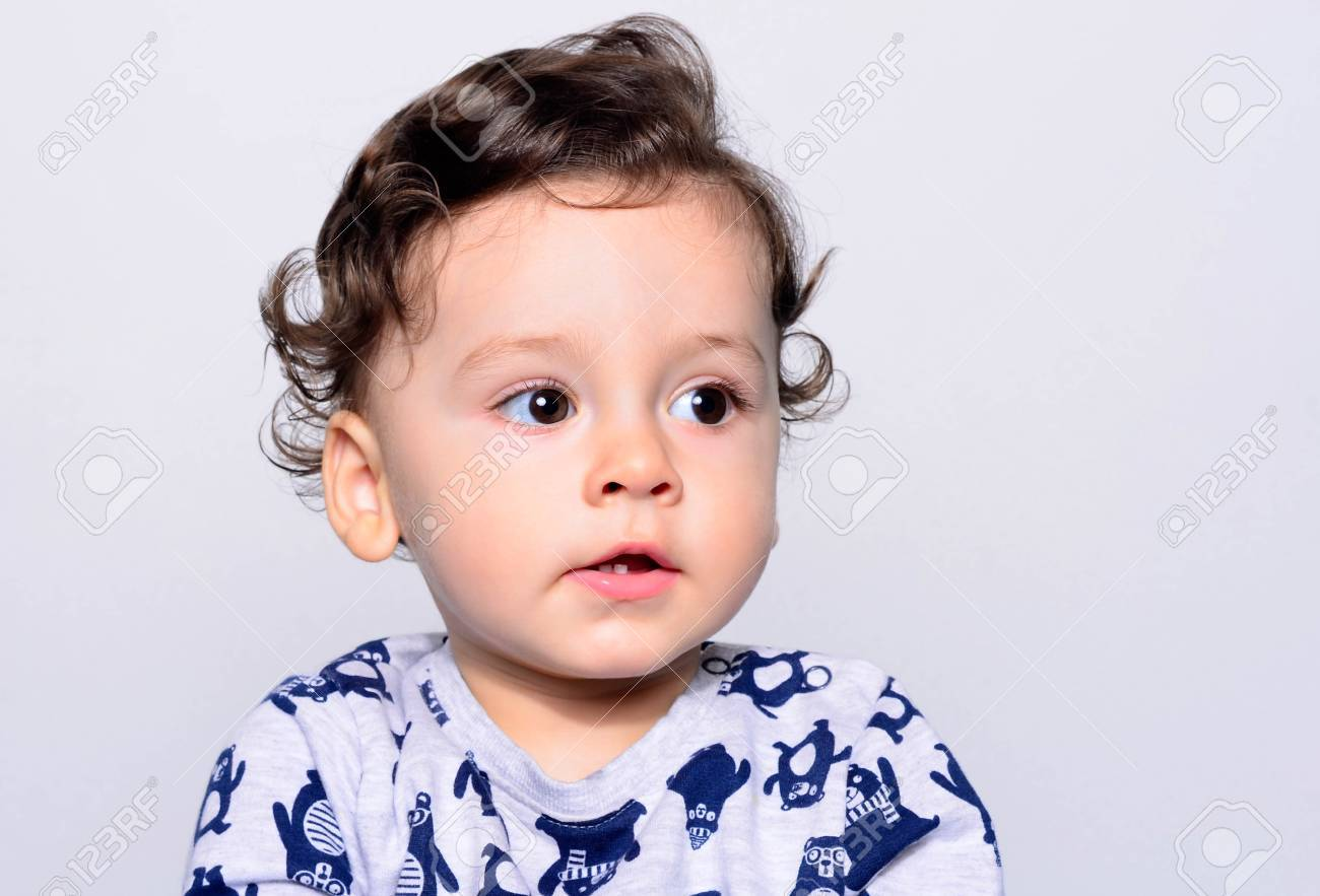 Portrait of a cute curly hair baby boy looking away. Adorable one year old  child