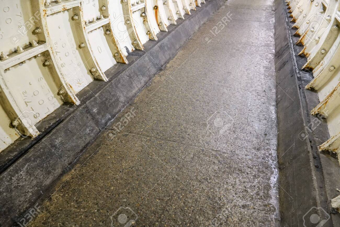 Flat stone floor and heavy iron plating on Thames under water tunnel wall. - 120898826