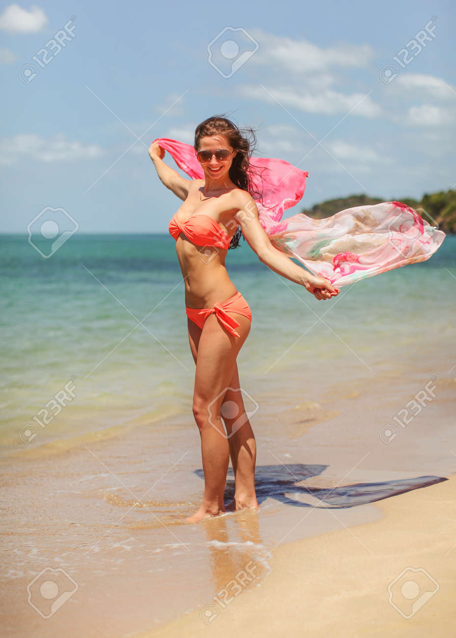 Young woman wearing bikini standing on wet sand at the beach, holding scarf waving in wind. Clear sea and sky background - 168512911