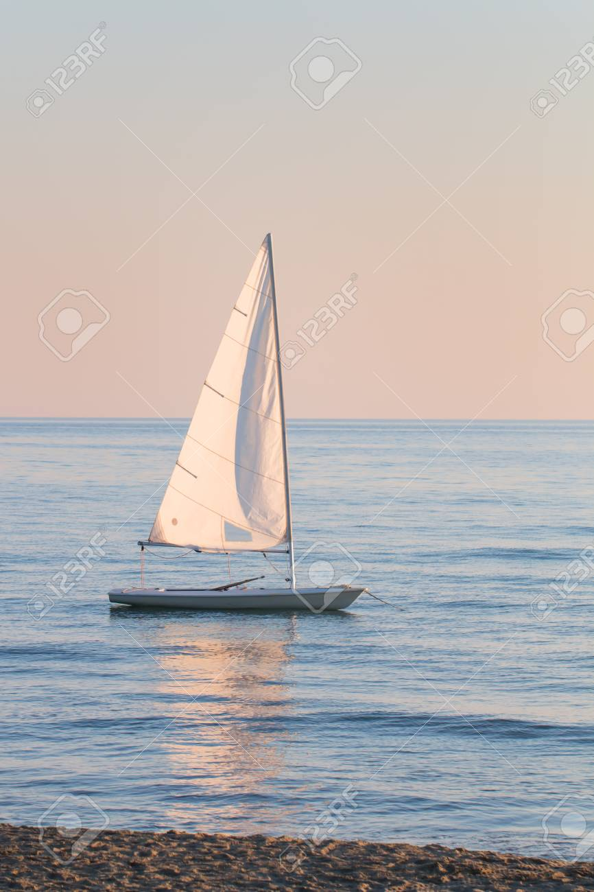small sailboat in the water anchored next to the beach in a summer