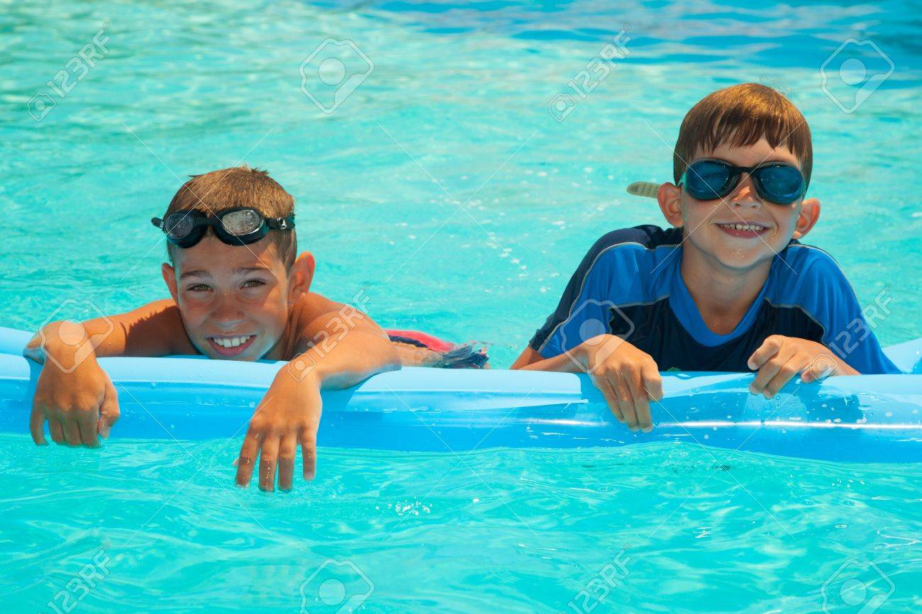 Two happy boys in the swimming pool. Blue water. Brothers Stock Photo - 15512972