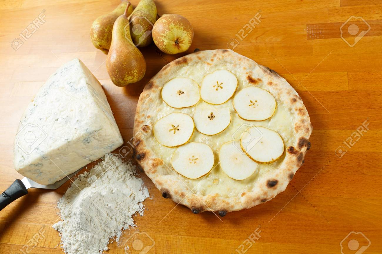 Typical Italian Pizza cooked in electric oven with ingredients in the background on a wood table Stock Photo - 17870194
