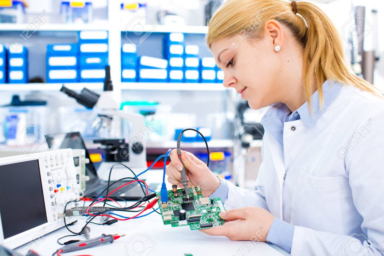 Engineer working with circuits. A woman engineer solders circuits sitting at a table. Microchip production factory. Technological process. Assembling the PCB board. Girl repairing electronic device on the circuit board. - 66767260