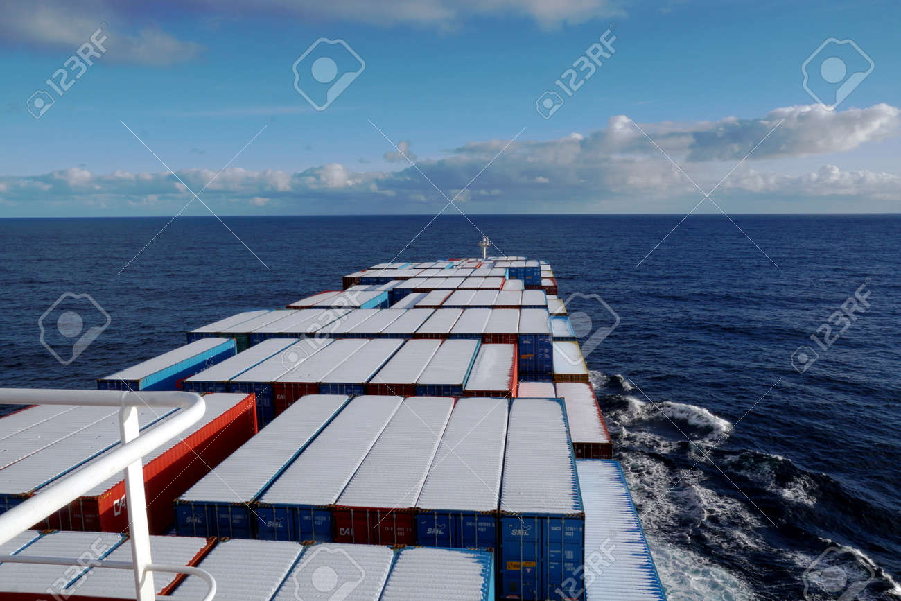 Container vessel covered with snow on top of the container sailing over the Pacific ocean during winter season. - 165659893