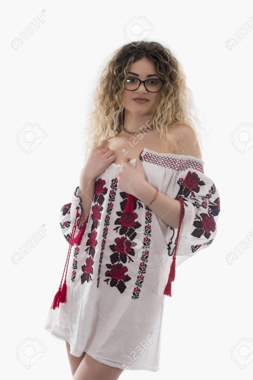 Woman With Curly Hair And White Dress With Red Flowers Posing