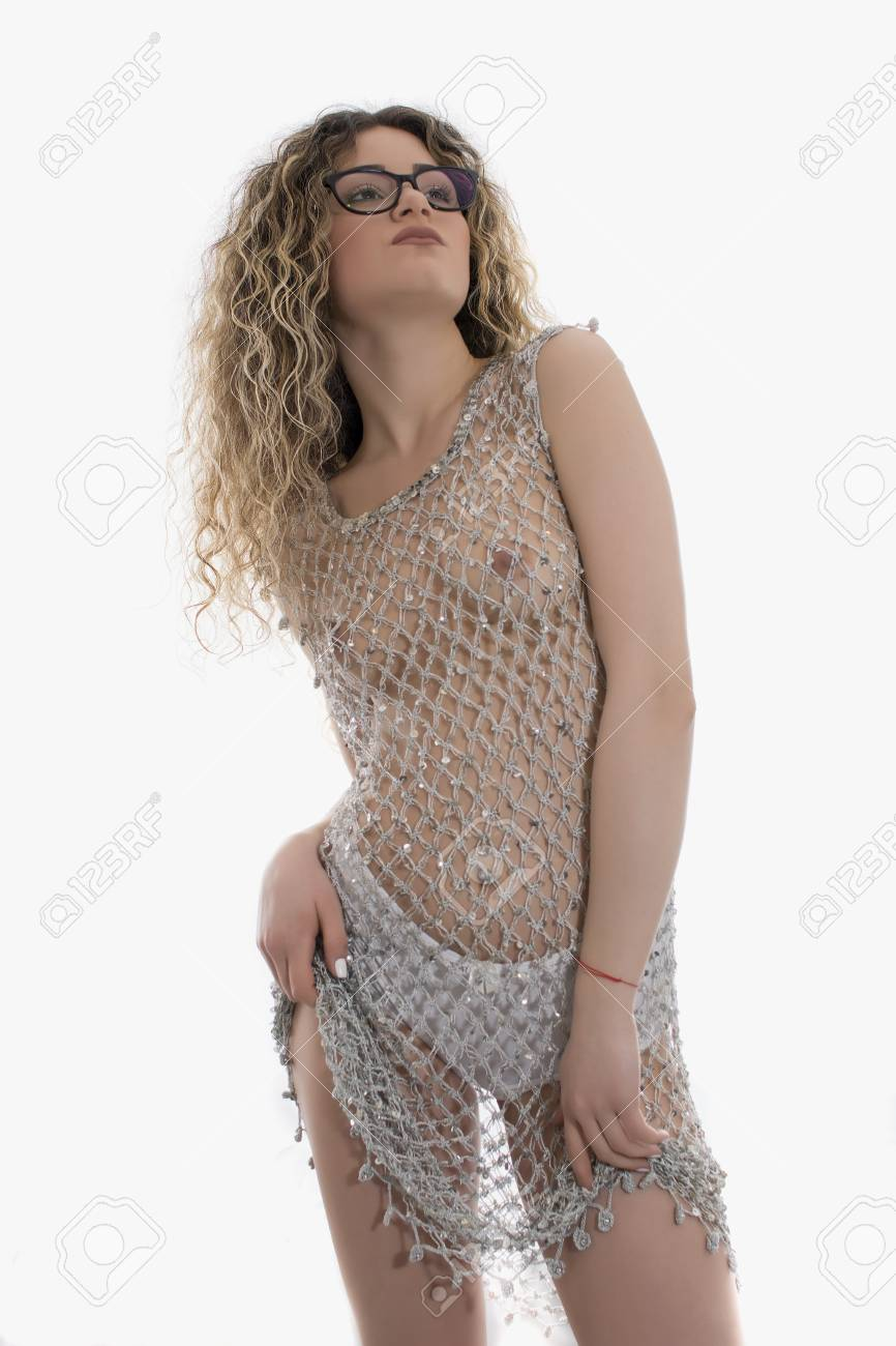 41e19d5fda5 Young girl with curly hair posing in a silver fishnet dress on white  background Stock Photo