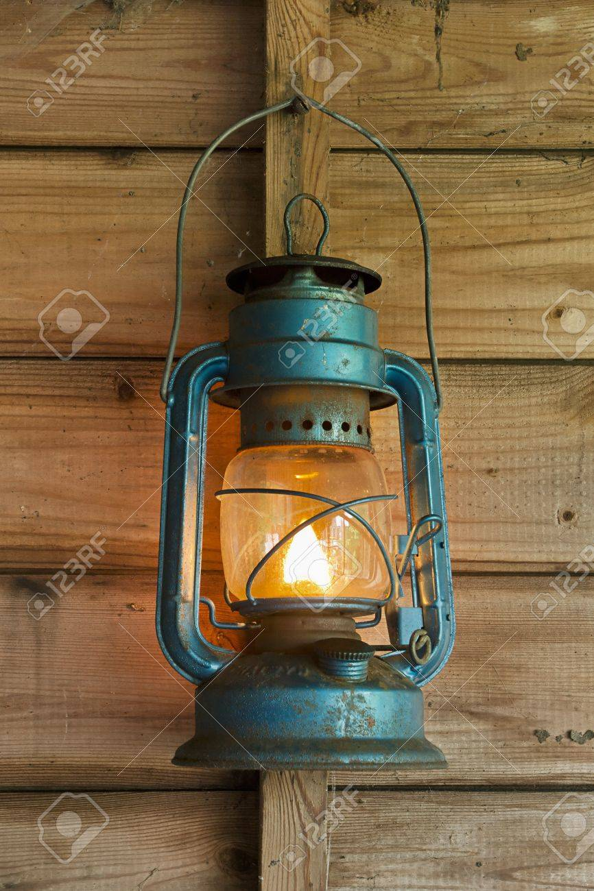Rusty Lit Blue Lantern Hanging In An Old Shed Stock Photo