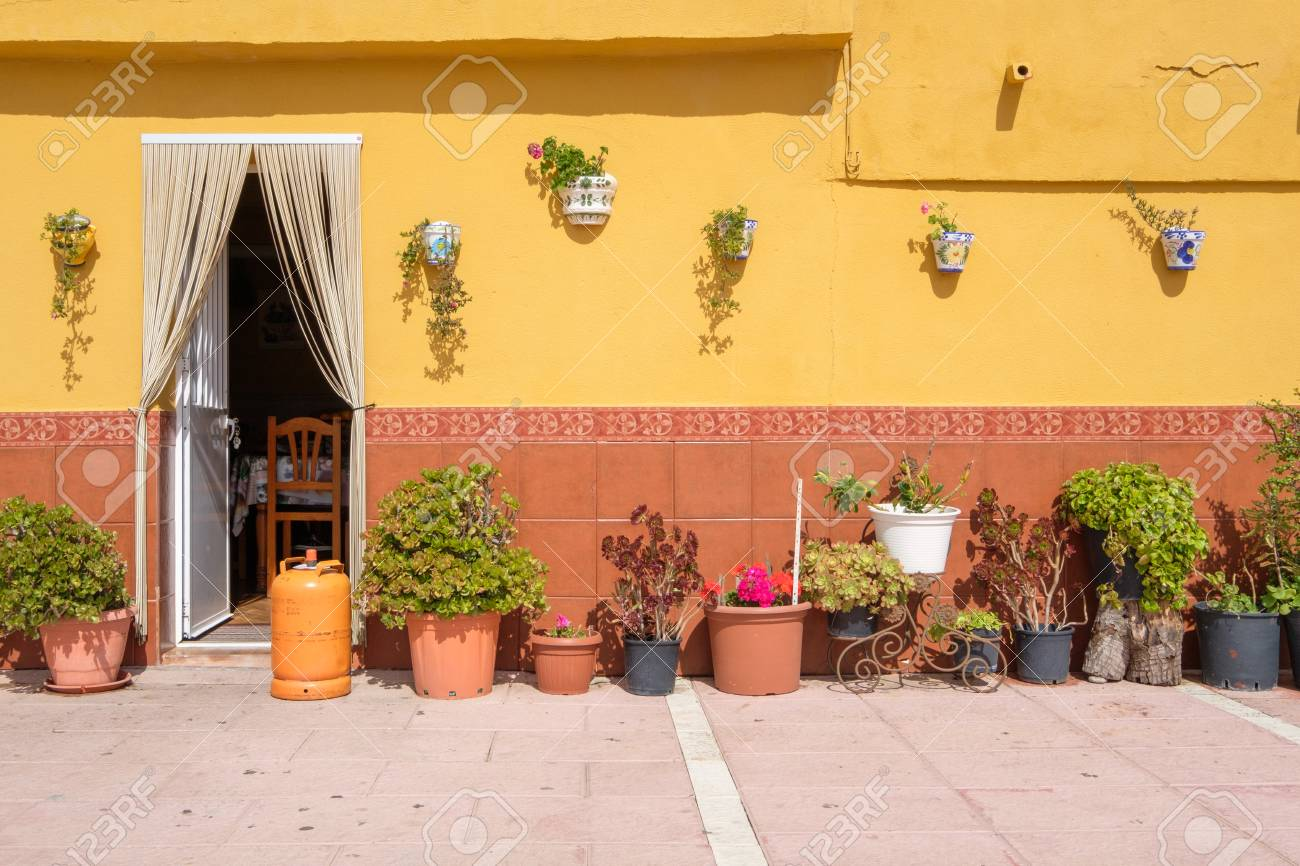 123RF.com & Traditional Spanish wall with lots of flower pots.
