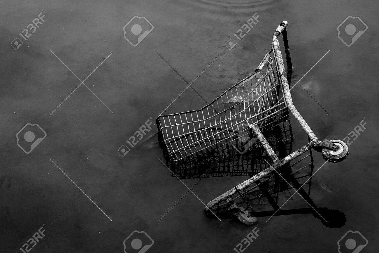 High contrast black and white photo of a shopping cart discarded in the sewer