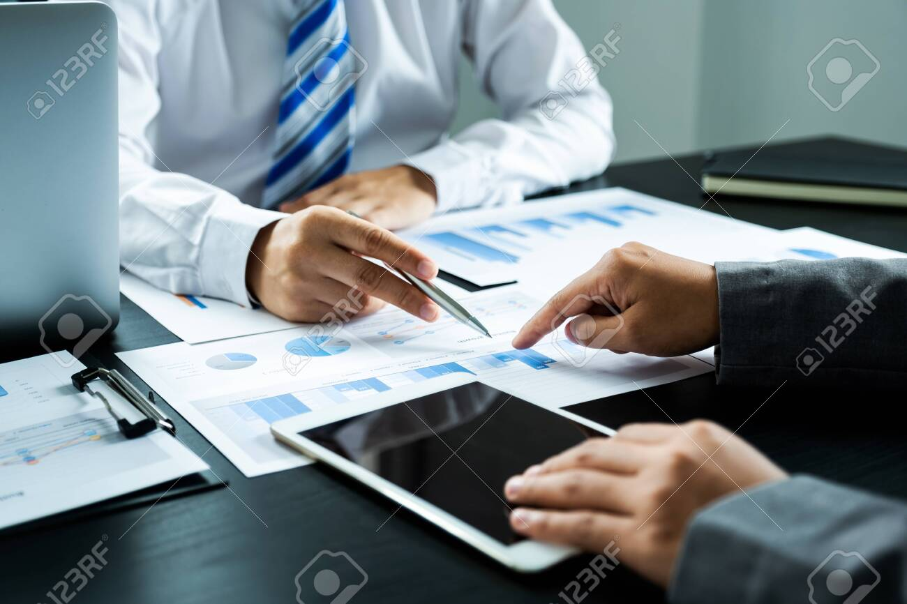 businessmen and businesswomen team pointing to charts meeting to plan strategies to increase business income. Have a brainstorming graph analysis and discussing for the new target success. - 150376564