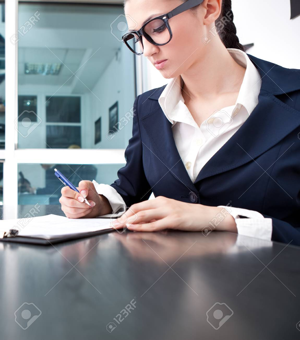 attractive young business woman writing a contract in office Stock Photo - 9617067