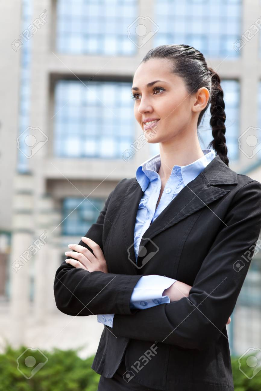 attractive businesswoman smiling while standing in front of an office building, vertical shot Stock Photo - 9653536