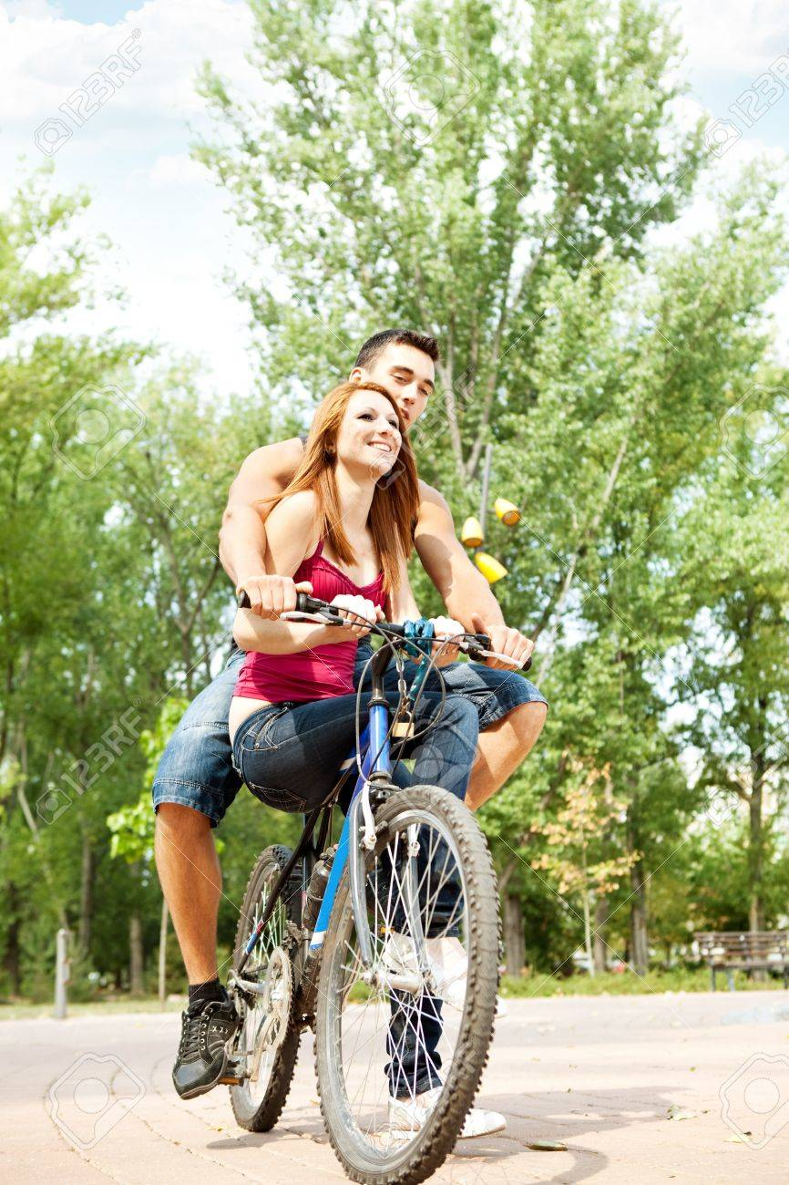 laughing couple on a bike in the park stock photo picture and