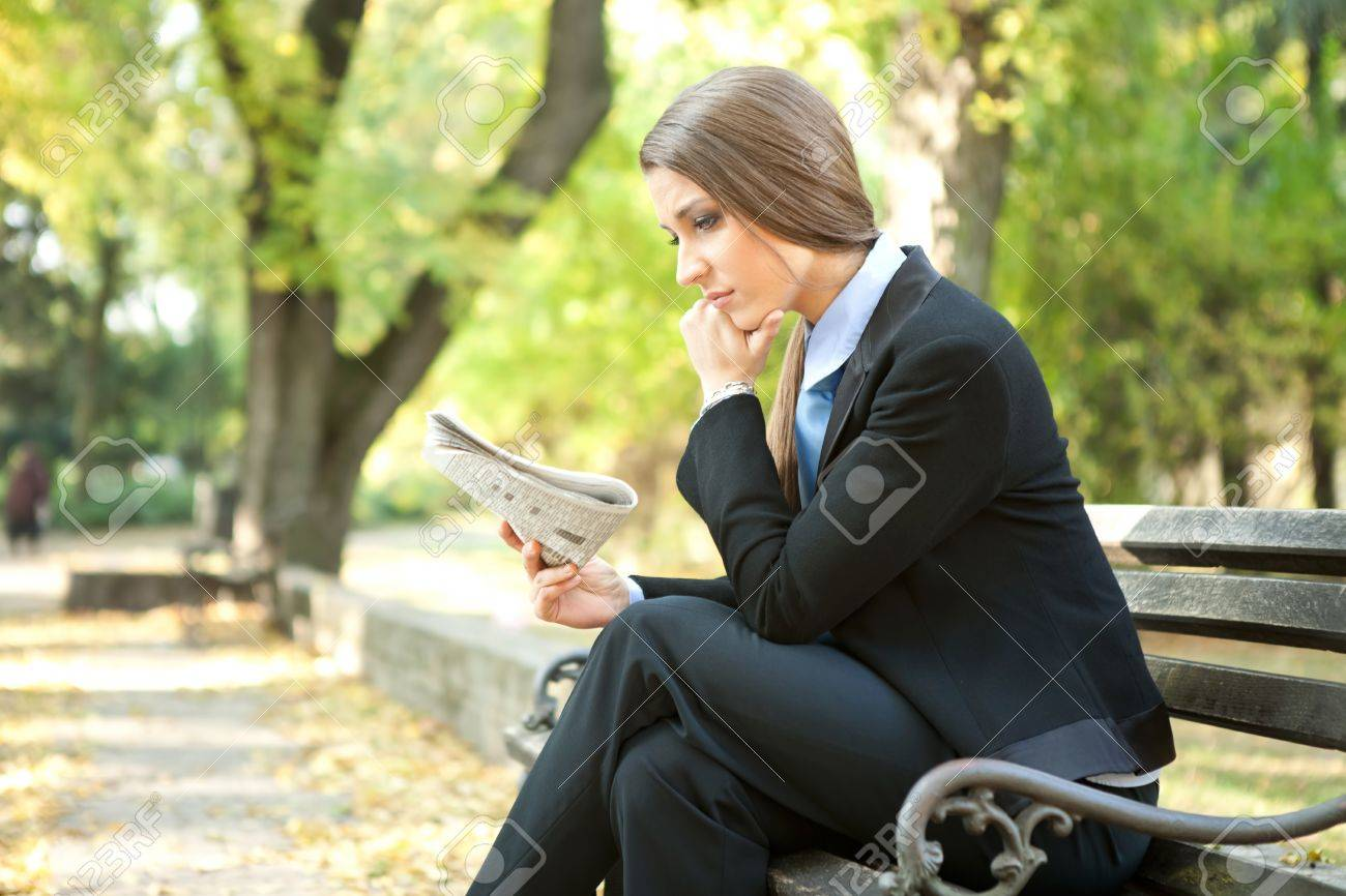 young thinking businesswoman reading newspaper , sitting on bench in park Stock Photo - 11504362