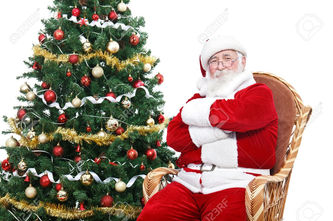 santa claus sitting in rocking chair with crossed arms and relax decorated christmas tree - Santa Claus Christmas Tree Decorating Ideas
