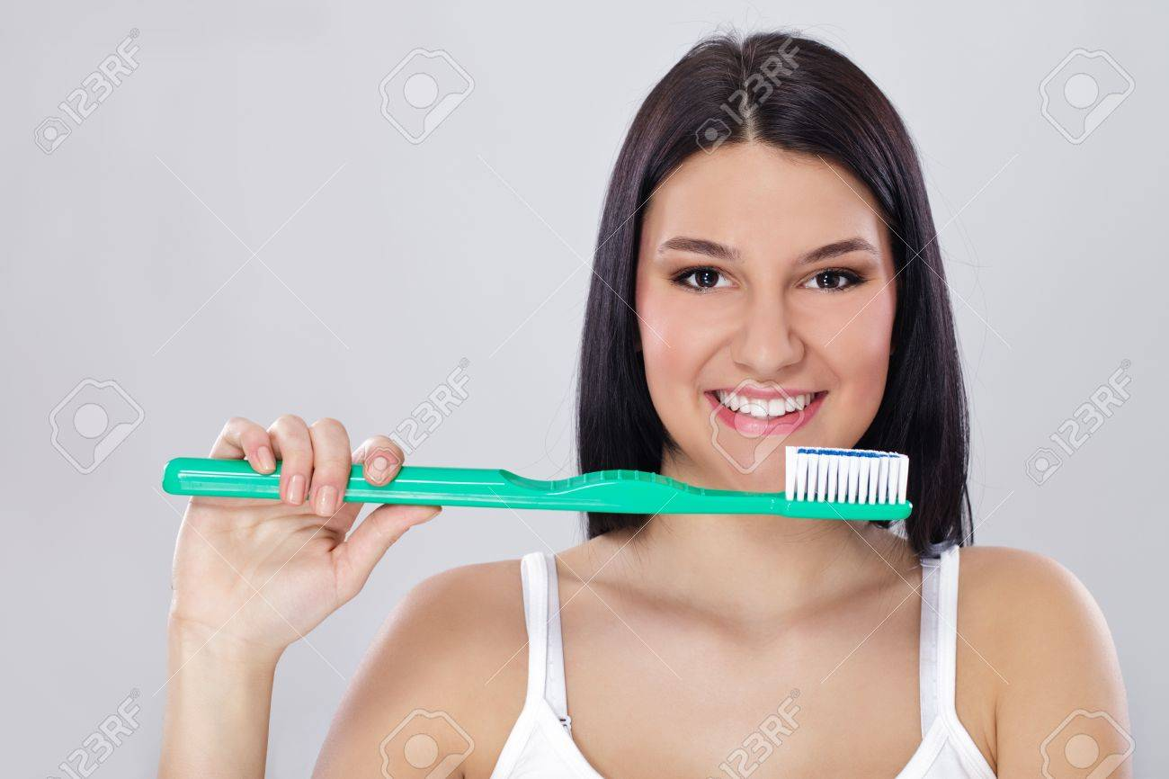 Young smiling girl with healthy teeth holding big toothbrush Stock Photo - 12781393